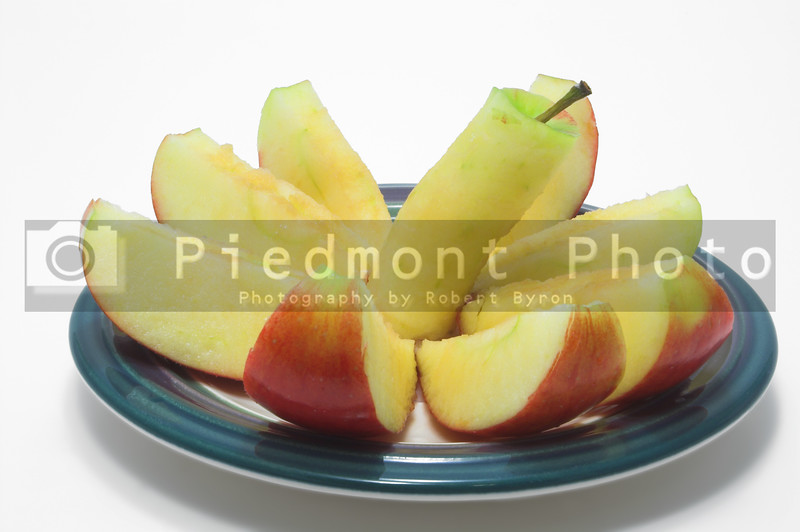 A red delicious apple sliced on a plate.