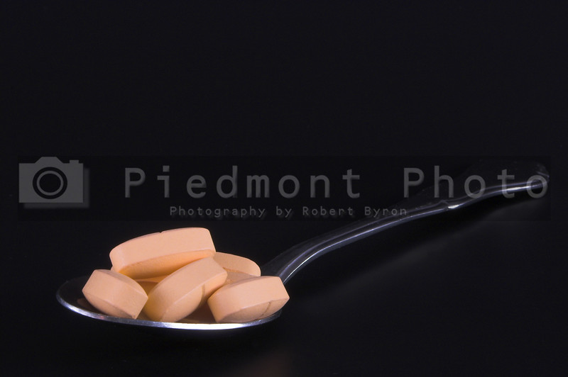 A teaspoon spoon filled with prescription pills.