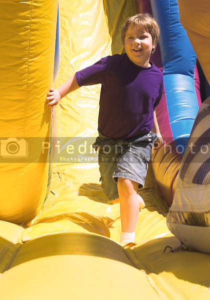 A young boy playing on a carnival obstical course.