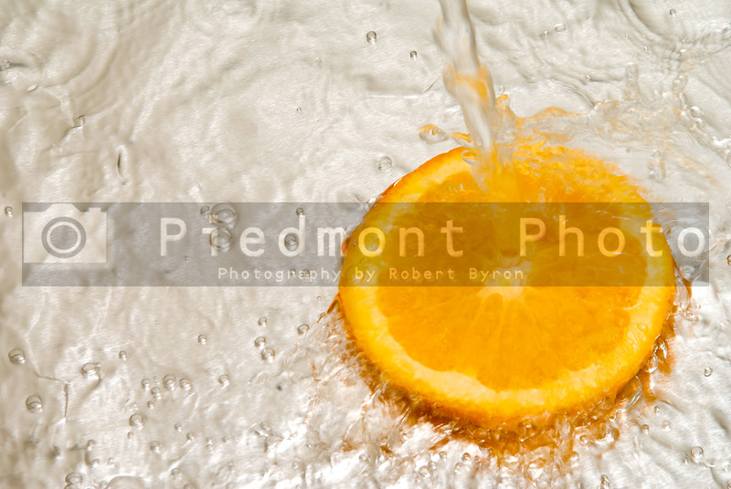 An orange slice under a stream of water.