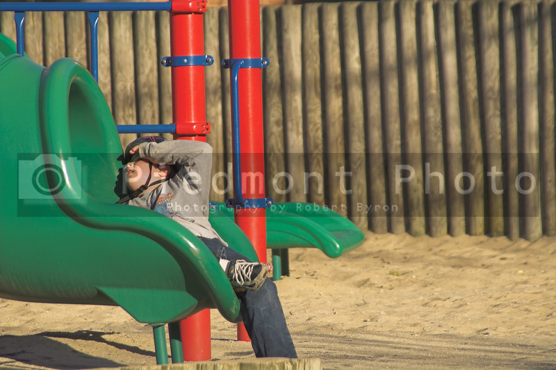 A young boy on a slide at a playground.