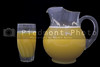 Orange juice in a drinking glass and a pitcher.