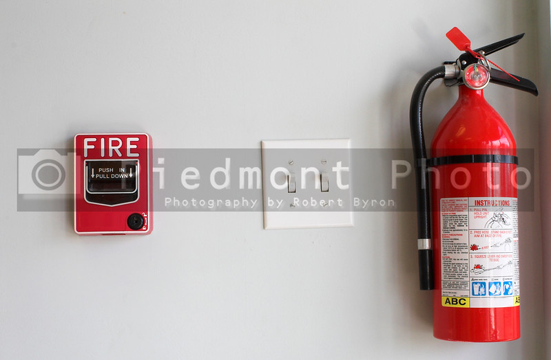 A fire alarm pull box and an extinguisher.