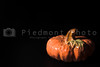 A ceramic pumpkin, harvest or halloween fall decoration in the shadows.