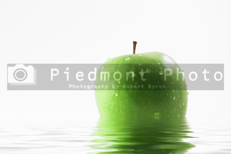 A wet apple sitting in water.