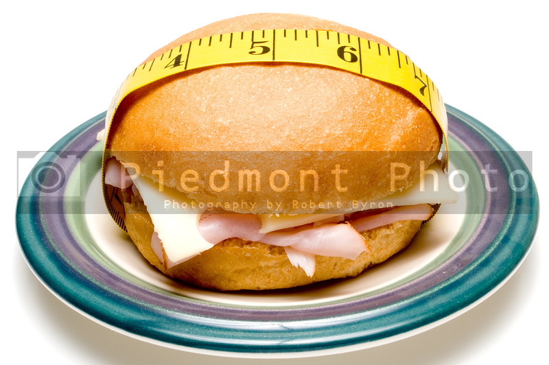 A ham and swiss cheese sandwich wrapped in a taolor's measuring tape.