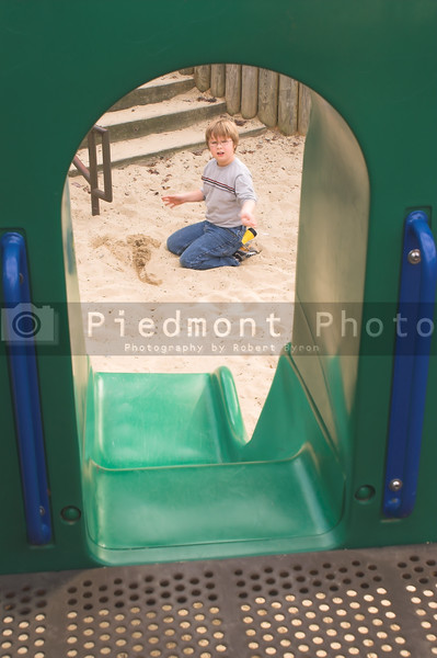 A little boy digging in the sand at a playground.