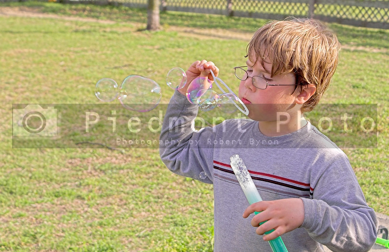 A young boy blowing bubbles in his yard.
