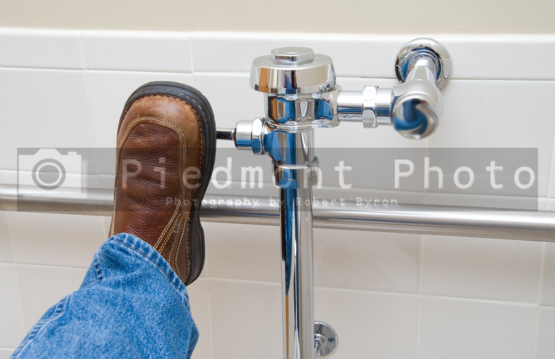 Flushing a Toilet with a foot in a restroom.