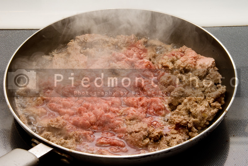 Hamburger meat browning in a pan on a stove.