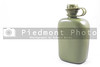 A military style olive green water canteen.