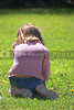 A little girl playing in the grass.