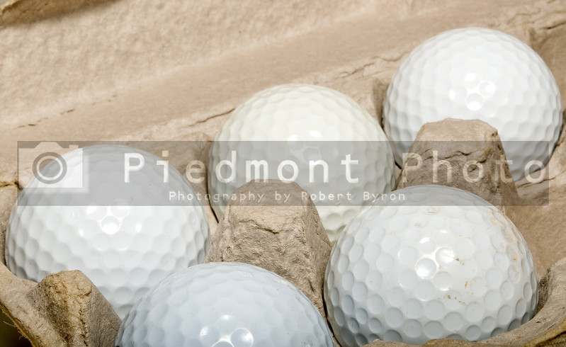 Several golf balls in an egg carton.