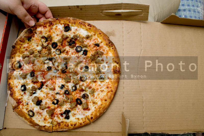 A sausage and balck olive delivery pizza.