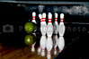 Several bowling pins and a bowling ball.