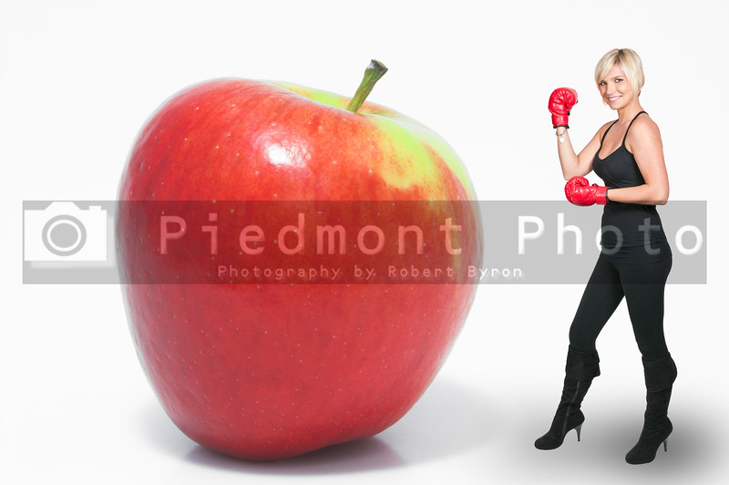A beautiful young woman wearing a pair of boxing gloves standing beside an apple