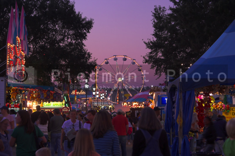 A brightly lit ferris wheel in motion at dusk.