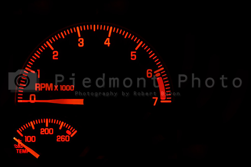 A red tachometer and temperature gauge on an automobile dashboard.