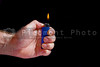 A person lighting a disposable butane lighter.