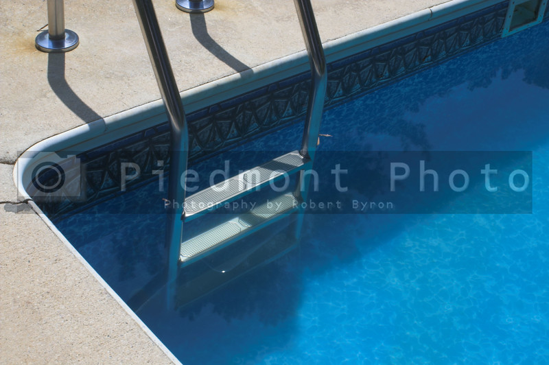 A ladder leading in to a pool of deep blue water.