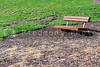 An empty bench on the lawn of a park.