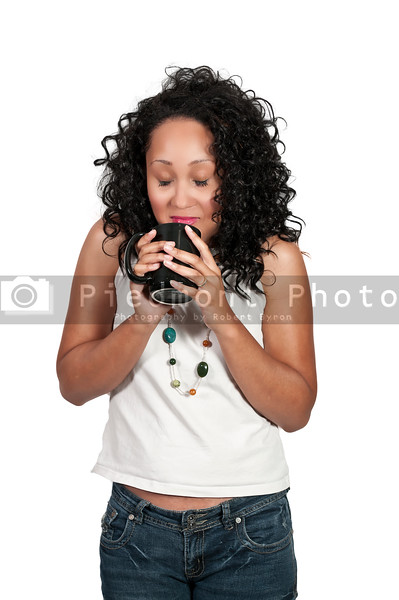 A beautiful young black woman drinking coffee.