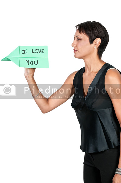 A woman throwing a paper airplane that says I Love You