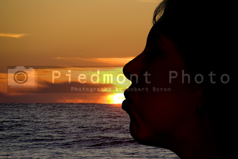 The silhouette of a woman kissing the sun