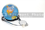 A globe of the Earth and a medical stethoscope.