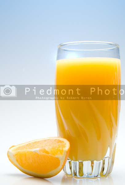 A glass of orange juice with an orange slice.