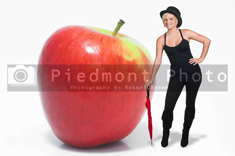A beautiful young woman in a top hat standing next to an apple