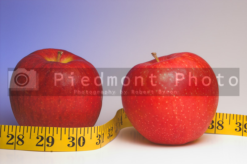 Two red apples wrapped in a tailor's measuring tape.