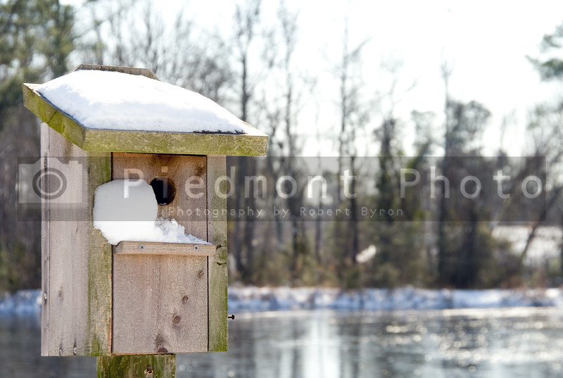 A wooden birdhouse covered in fresh snow.