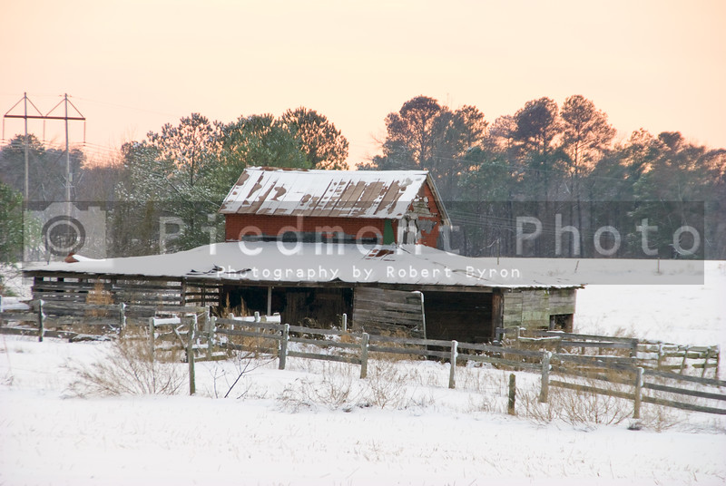 An old horse stable and corral in the snow.
