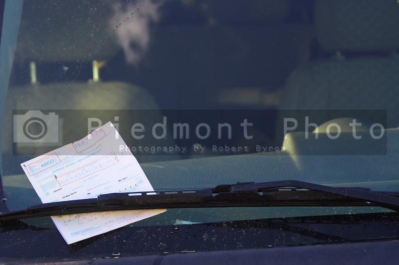 A parking ticket loving placed under the windshield wiper of a car.