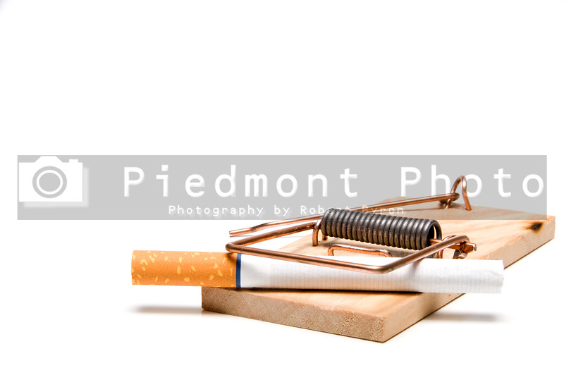 A cigarette caught in a wooden mousetrap.