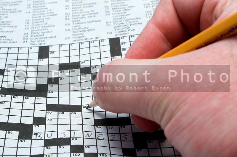 A man doing a newspaper crossword puzzle.