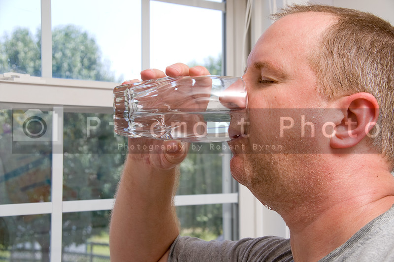A man drinking a glass of water.