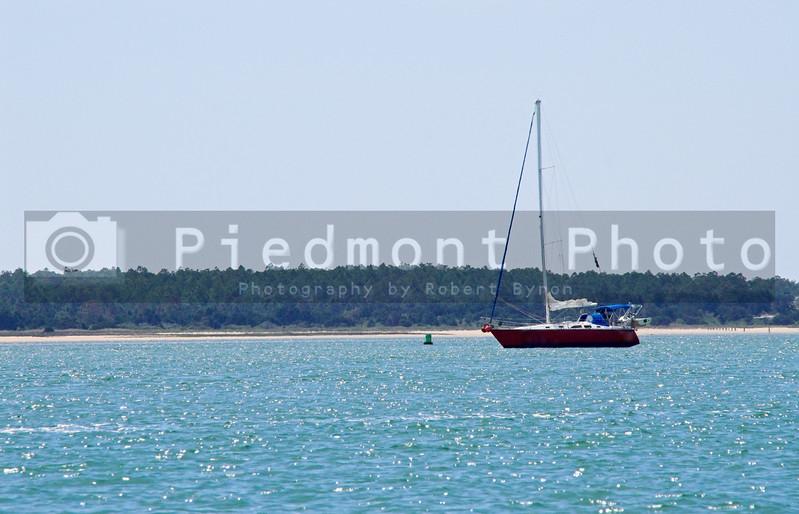 A sailboat securely anchored at the seashore.