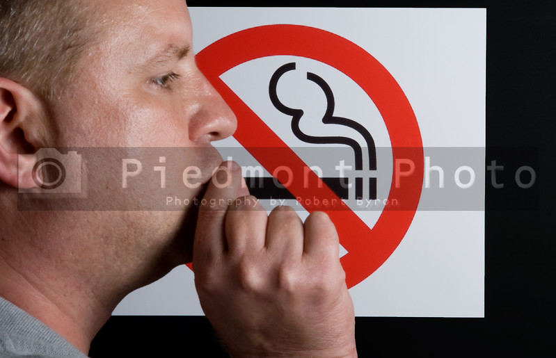 A man smoking a no smoking sign.