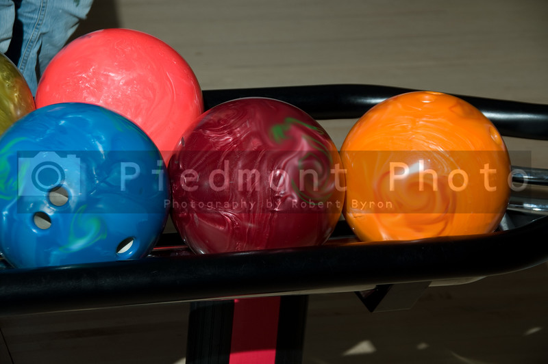 Bowling balls ready to be rolled down an alley.