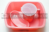 A pink medical wash basin, kidney tray and water pitcher.
