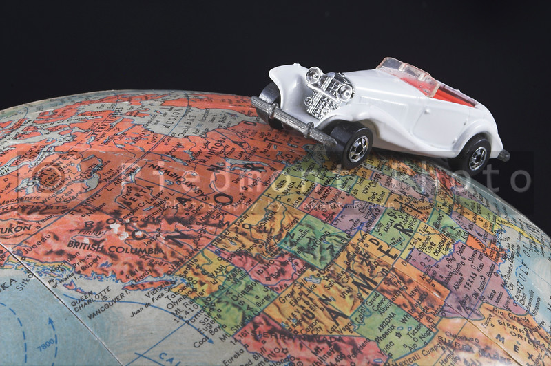 A toy car on a globe - world travel concept.