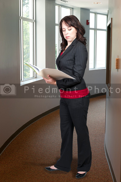 A beautiful young woman lawyer in a business suit holding a manila file folder