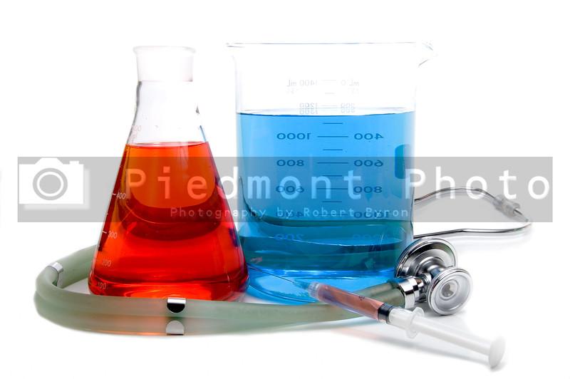 Medical Beakers Syringe and Stethoscope on a white background.