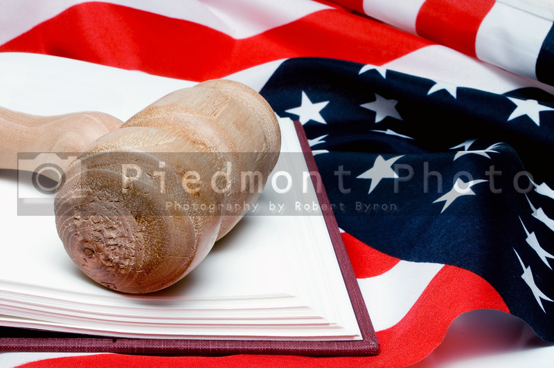 An open law book and a judges gavel on an American flag.