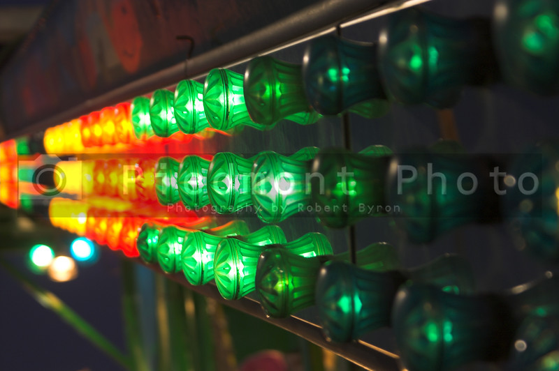The bright and colorful lights on a carvival ride.