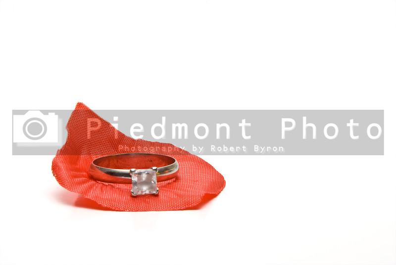 A diamond wedding ring on a fake rose petal.