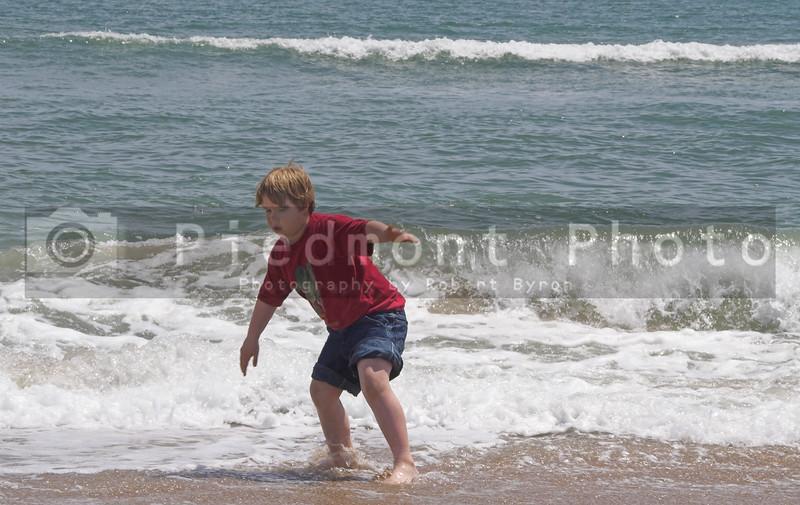 A young boy playing at the seashore.