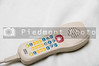 A TV remote control with a nurse call button.